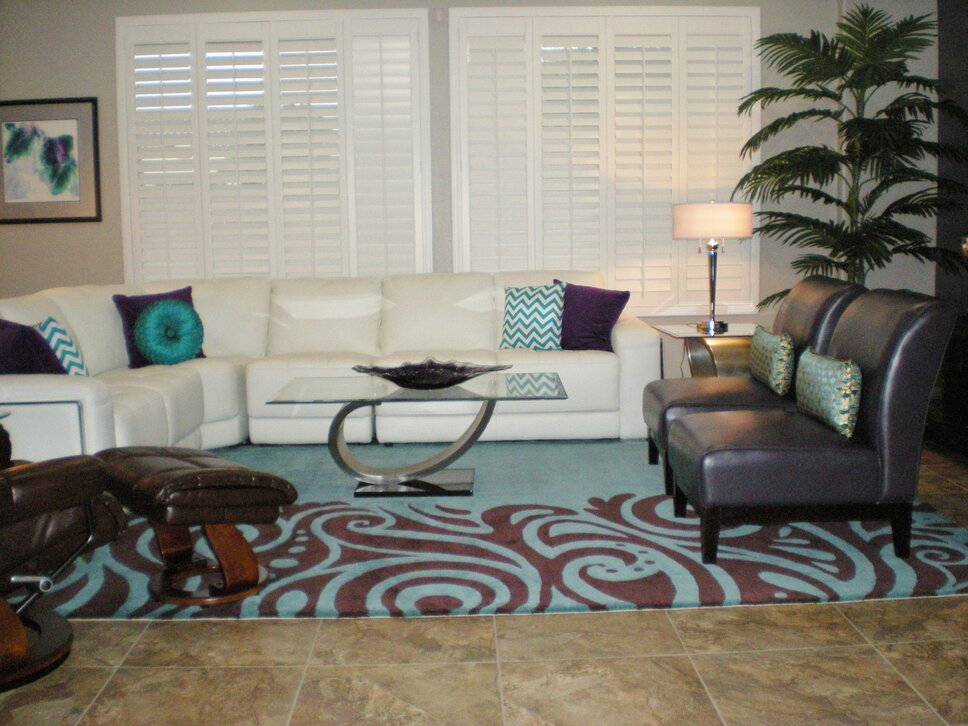 The beautiful area rug defines and anchors the space adding a soft touch to the travertine floors. The owners wanted to be able to seat a minimum of 8 people in the living area so slippers chairs were added and bring a pop of color. Contemporary Living Room design
