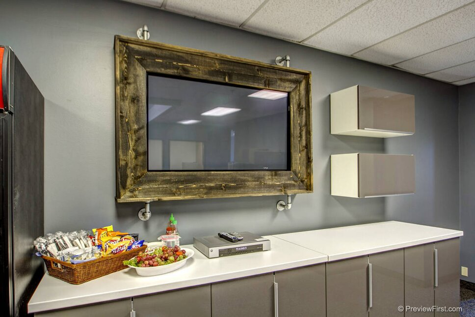 A custom built tv frame to match the rustic meetingdining table. Hung with pipe fittings for an industrial look.  SAN DIEGO OFFICE DESIGN  www.sdofficedesign.com Industrial Commercial design
