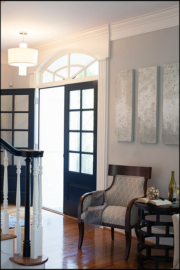 Century furniture, original artwork, navy blue front door, black banister Contemporary Entryway & Hallway design