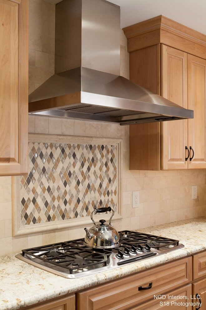 A multi-colored tile accent breaks up the backsplash behind the drop in stove top. Nina Green, NGD Interiors Traditional Kitchen design