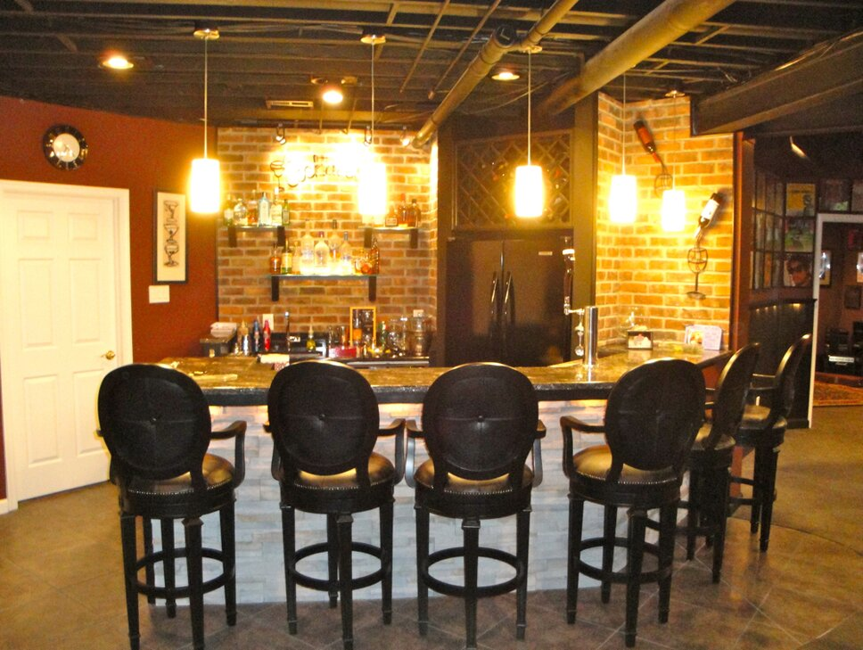 Stacked stone bar with granite top and under mount lighting used to highlight stonework.  Real brick walls and open, painted ceiling to allow height in space and industrial feel.  Modern lighting added needed glow to space. Contemporary Rec Rooms design