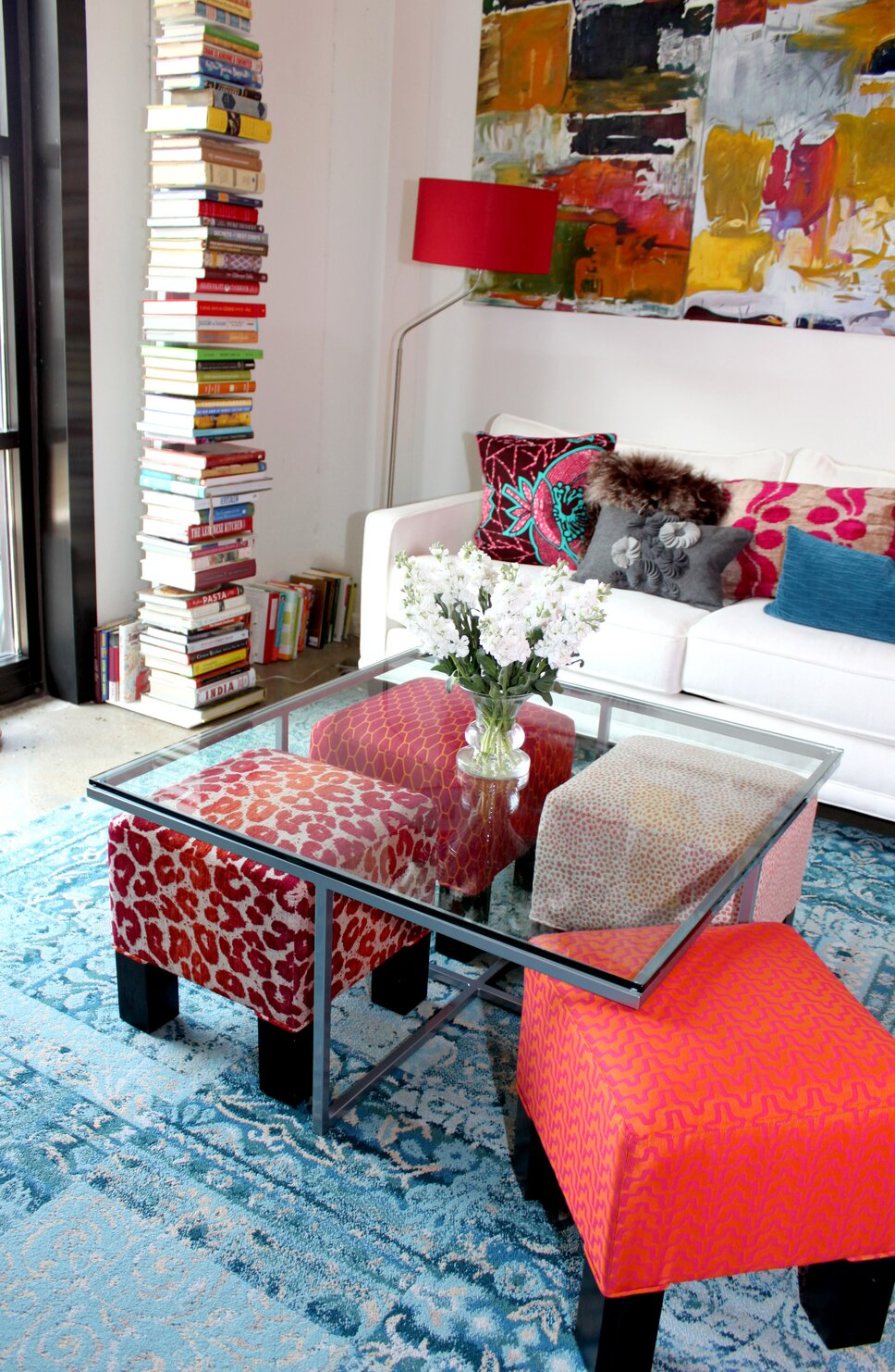 This space is designed with the clients description words- bohemian and contemporary. She requested pink  to be the dominate color. We created a contemporary feel with the velvet sofa in white and white walls, adding ethnic patterns in the rug, pillows and ottomans. Photo credit Laurl Self Modern Living Room design