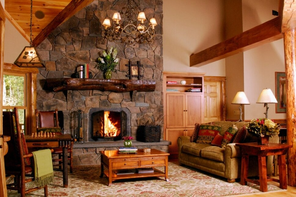 A rustic Andirondack style great room with a fieldstone fireplace facade, log posts, custom furnishings and lighting. 