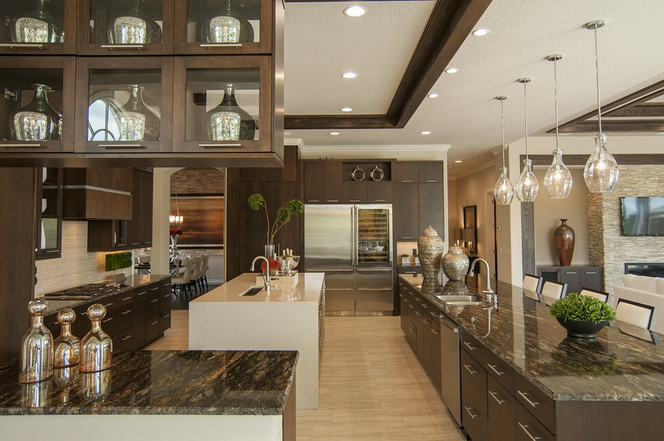 Clean lines, mult-function and clever details are the highlight of this award-winning kitchen design. Featuring separate workstation island of waterfall design quartz cambria, oversize seating island in exotic Kosmos granite, and multi-level espresso cabinets. Contemporary Kitchen design