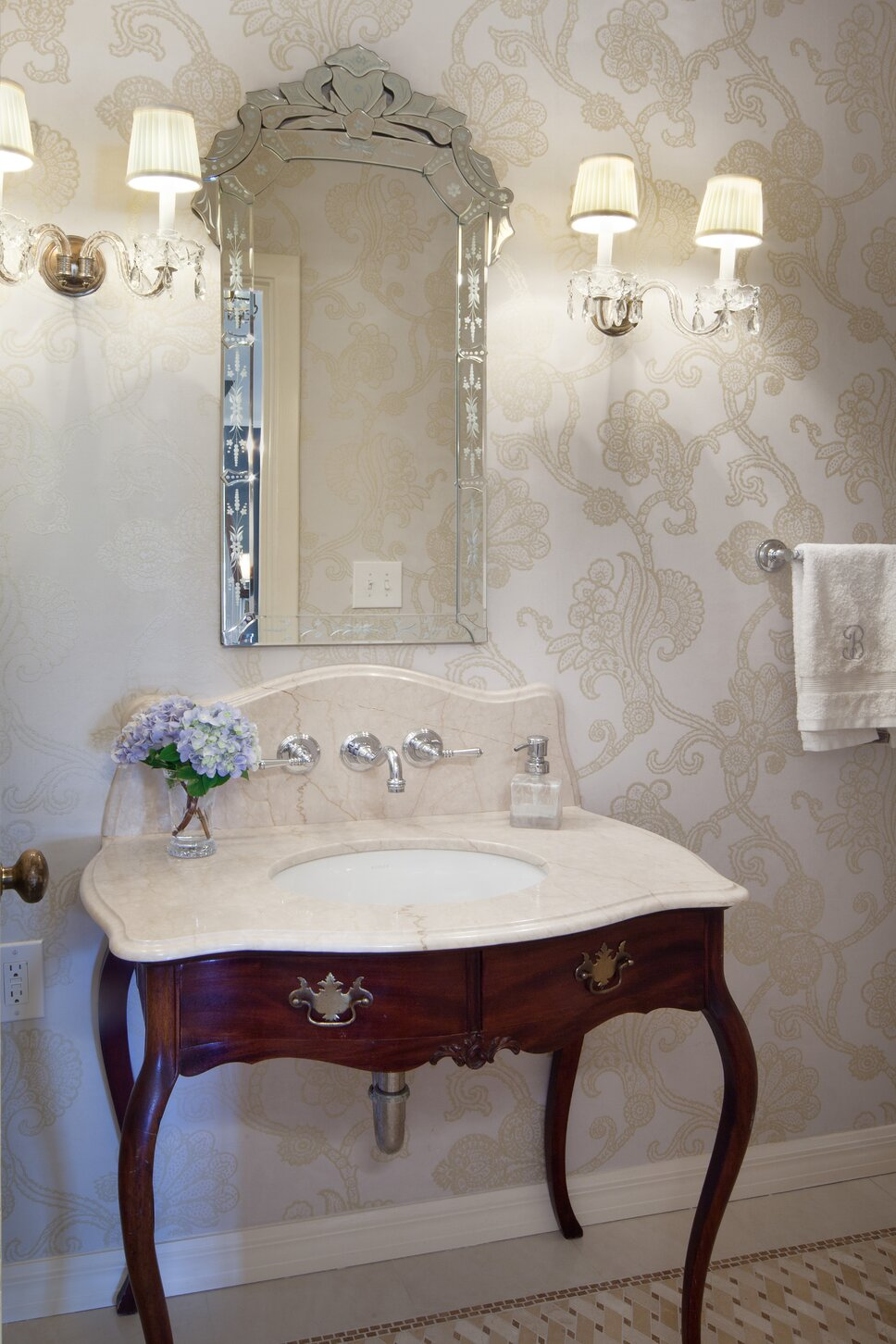 Powder Room with repurposed antique as vanity, venetian style mirror and vintage crystal sconces set against a muted blue and gold wallpaper Traditional Bathroom design