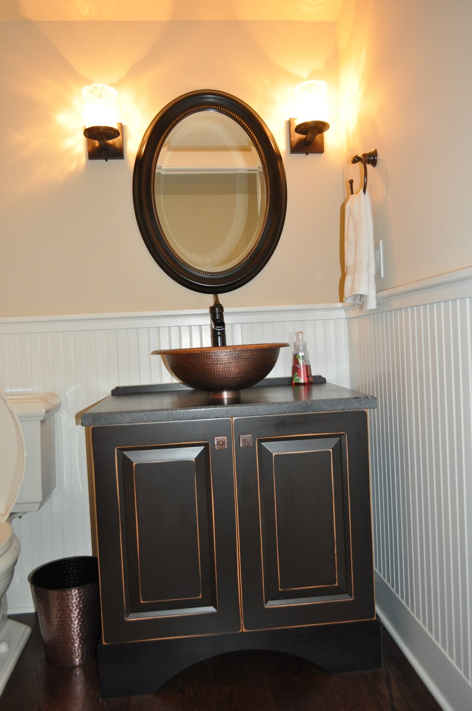 The hammered copper sink is elegant with the custom rubbed black cabinet. Contemporary Bathroom design