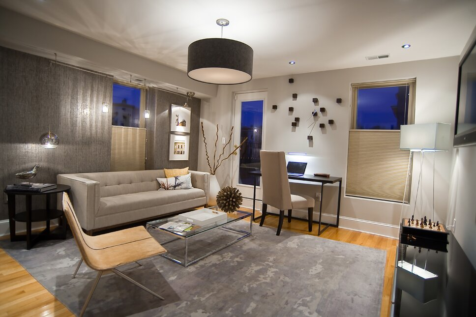 This bachelors sitting room was re-designed to create a contemporary space in a century old townhome in Washington, DC. We used a grey pallette to create the masculine, sleek and tailored feel that the client asked for. We used a Gus Modern sofa, elegant raw hide chair and minimalist writing desk. We covered the back wall in a metallic weave Phillip Jefferies wall paper, highlighted with modern lighting. Contemporary Home Office design