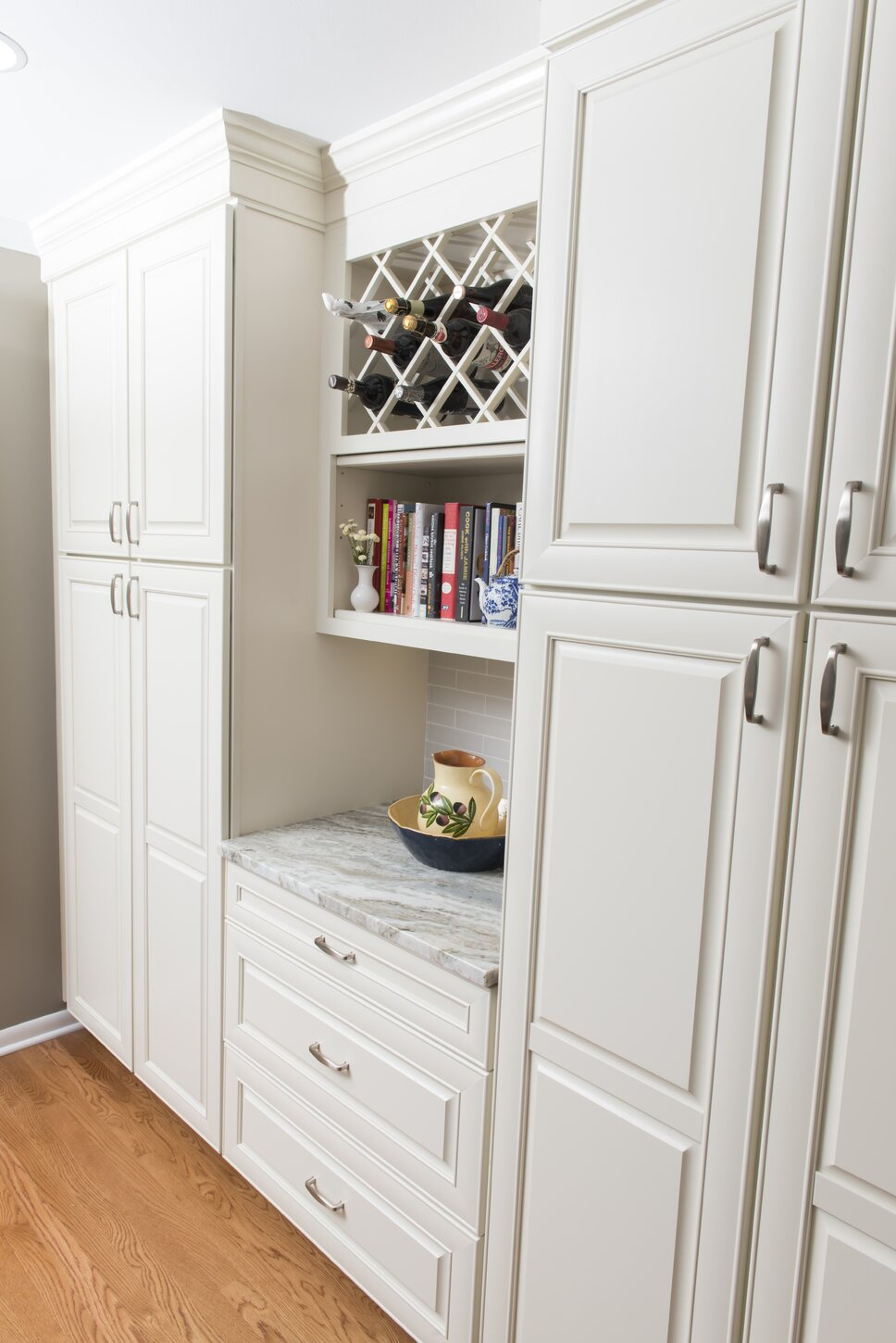 We created a beautiful area of built in pantries, separated by a wine rack and book shelves, as well as a counter space for the homeowner to plan her menus and serve a glass of wine. Contemporary Kitchen design