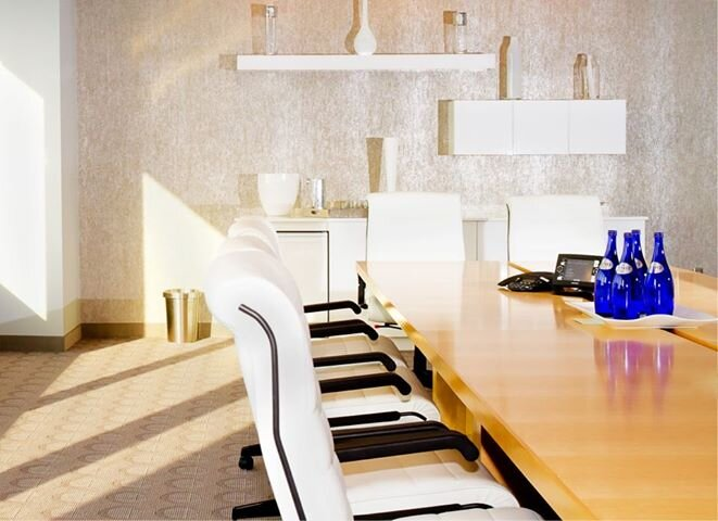 The boardroom reflects light using white gloss custom cabinets against silver textured wallcovering and lighting on the back of cabinets, maple table and white leather conference chairs. The accent lighting (not shown) is cubes colbalt blue. Sleek and upscale yet, perfect for a meeting or seminar. Contemporary Commercial design