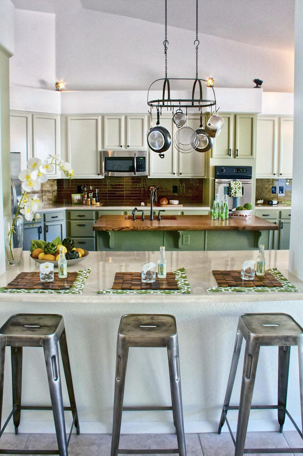 Southwest two-tone cabinetry with contrasting bronze-gold leaf backsplash.  Marble counter tops with wood counter top over island.  Stainless appliances, Oil Rubbed Bronze Fixtures. Cottage/Country Kitchen design