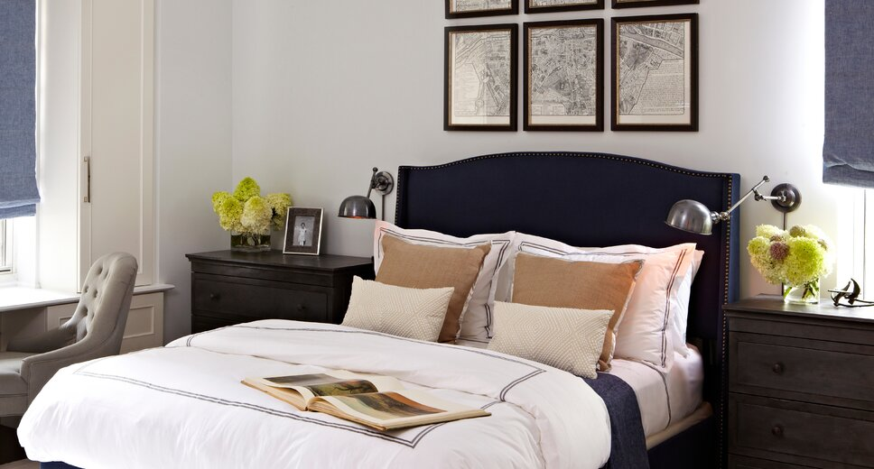This master bedroom is headed by this tall navy blue upholstered and studded headboard. Zinc dressers are used as nightstands. Light silk rug is used to anchor the room and amplify the amount of daylight which filters in. Motorized window treatments in a soft chambray blue is used to soften the room and carry the blue details throughout. Crisp white linens are paired with large soft silk pillows. 
