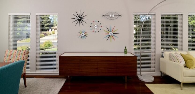 The sideboard sits beneath mid-century modern multicolor clocks. The dining chairs add a pop of color with the head chairs in fun multicolor and blue chairs. Modern Living Room design