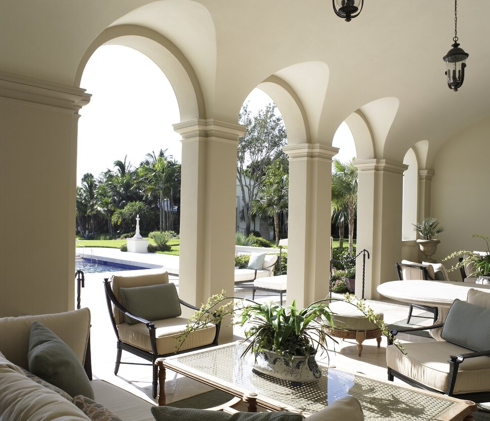 Mediterranean-inspired outdoor seating area with a mix of teak and cane furnishings. The groin vaults in the architecture were incorporated both inside and out. Traditional Exterior, Deck, & Patio design