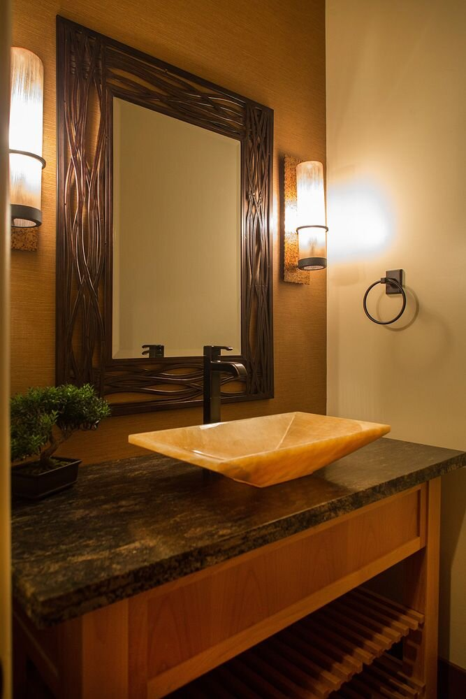The warm powder room has an onyx sink on top of kosmos granite.  The reed mirror is flanked by tall bamboo sconces. Contemporary Bathroom design
