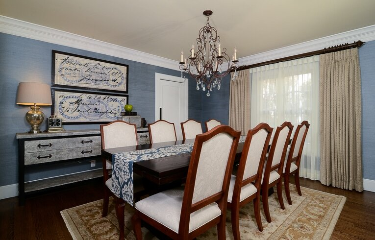 The Blue grasscloth wallpaper is perfectly accented by the table runner and stamp artwork above the console. Traditional Dining Room design