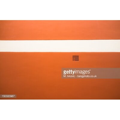 GettyImagesGallery Red Wall with White Stripe and Grate Detail by M. Ivkovic Photographic Print